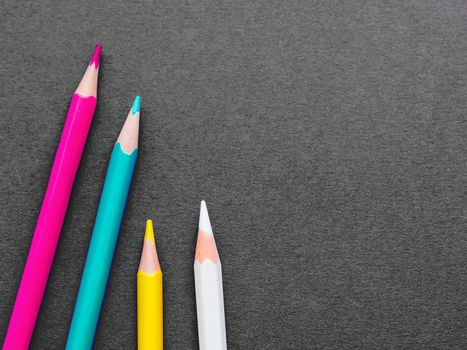Row of colorful watercolor pencils on dark grey paper background. School supplies on blackboard. Kid's stationery. Back to school black backdrop.