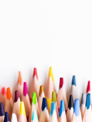 Vertical row of colorful watercolor pencils on white background. School supplies. Kid's stationery with copy space. Back to school backdrop.