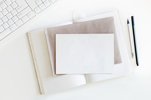 Top view on white table with keyboard, copybook with blank pages, craft envelope, clear postcard and pen with pencil. Flat lay.