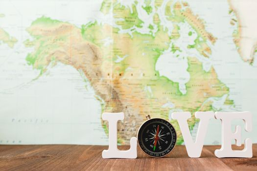 Love to travel. Magnetic compass and blurred world map as backgr