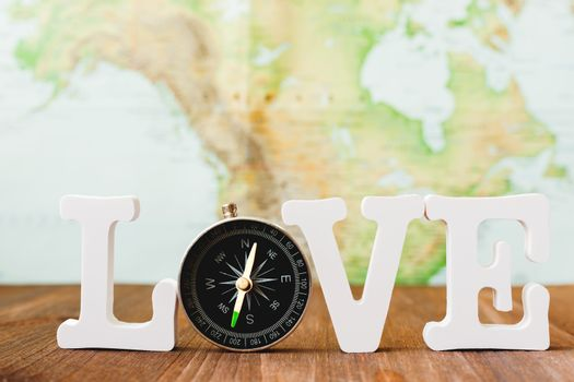 Love to travel. Word with magnetic compass. Blurred world map as