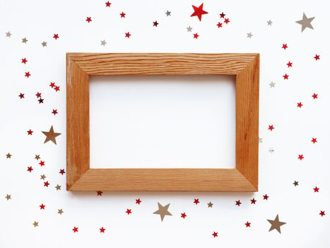 Shabby wooden photo frame on white background with scattering st