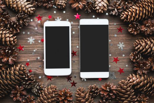 Rustic wooden background with two smartphones and Christmas deco