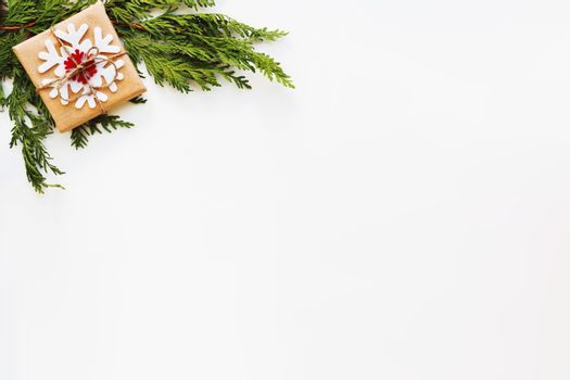Christmas and New Year background with arborvitae branch and present wrapped in craft paper with snowflakes. Flat lay, top view. Place for text.