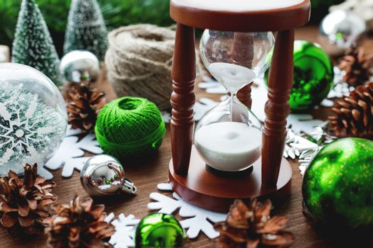 Christmas and New year background with presents, ribbons, balls and different green decorations on wooden background. Wooden sandglass measures time till holiday.