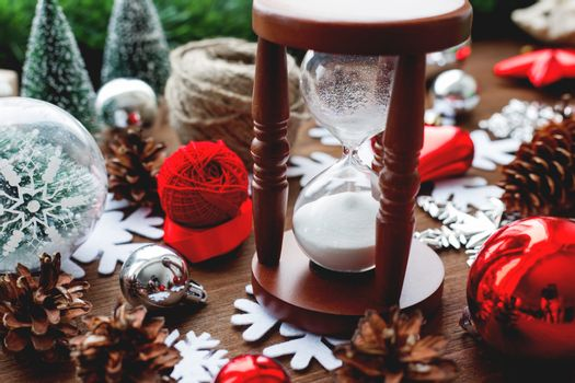 Christmas and New year background with presents, ribbons, balls and different red decorations on wooden background. Wooden sandglass measures time till holiday.