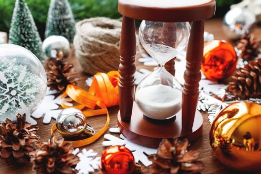 Christmas and New year background with presents, ribbons, balls and different yellow and golden decorations on wooden background. Wooden sandglass measures time till holiday.