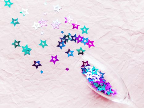 Transparent wine glass with magenta and cyan colored spangles. Festive copy space with crockery on crumpled pink paper background.