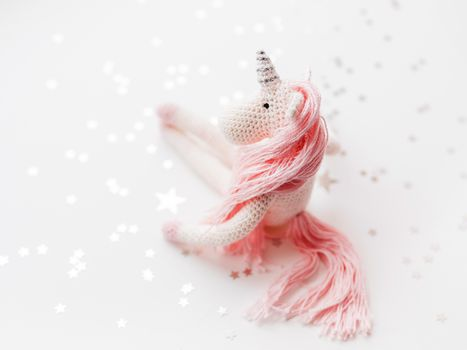Cute fairy unicorn with a pink mane and a tail made of threads.