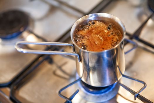 Coffee is brewed in a cezve on gas stove. Hot beverage in metal turka.