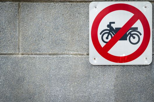 Motorcycle no entry sign install on concrete wall in front of tu