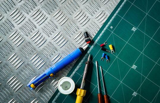 Soldering tools. Soldering iron, spool of soldering wire, screwd