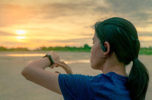 Asian woman wear in ear sport true wireless earbuds touching sma