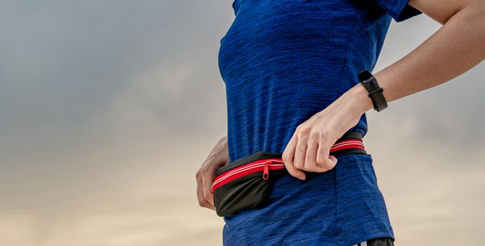 Young Asian woman wear wristband and waist belt. Running cardio