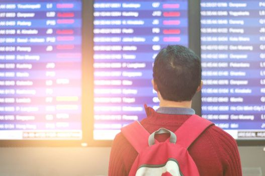 Travel airport tourist man looking for cancelled flight  at airport terminal screens . Covid-19 or Coronavirus concept.