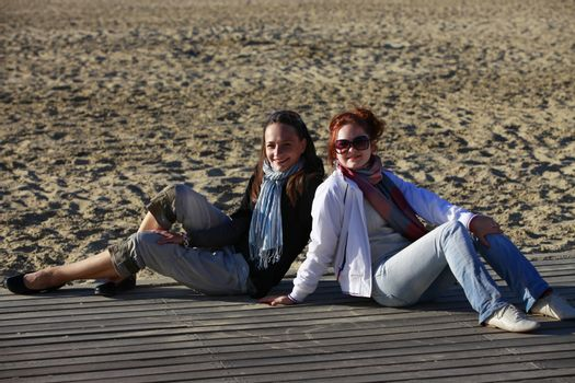 Two girls sits on the wooden bridge at beach
