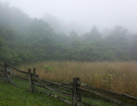 Wooden rail fence along foggy field on Blue Ridge Parkway.