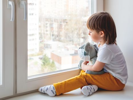 Toddler boy sits with teddy bear in medical mask. Kid with plush toy look through window outside. Koala bear and child on home quarantine because of coronavirus COVID-19.