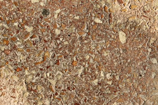Reddish conglomerate rock grains texture on a rough surface