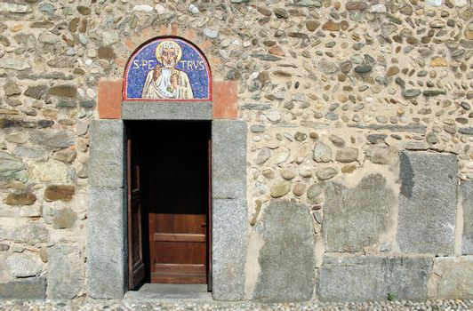 Door and mosaic lunette on the facade of a romanesque italian church