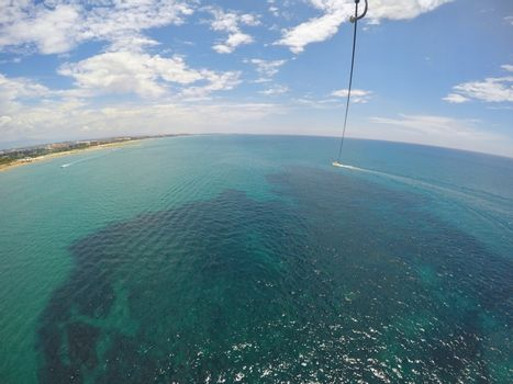 View from above of speedboat dragging  parachute