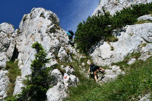 Teens climbing on the rocks in alpine area of Piatra Craiului mountains, Romania