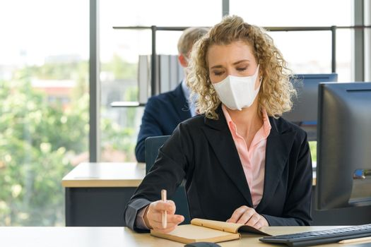 Young blonde staff in a suit with a face mask is taking notes of what to do after the meeting. Reduce the spread of Coronavirus disease 2019 (COVID-19) in the office.
