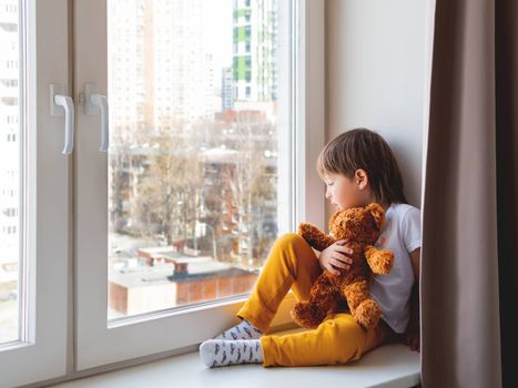 Toddler boy sits with teddy bear. Kid with plush toy look through window outside. Koala bear and child on home quarantine because of coronavirus COVID-19.