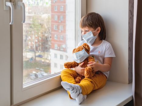 Toddler boy sits with teddy bear in medical masks. Kid with plush toy look through window outside. Browh plush bear and child on home quarantine because of coronavirus COVID-19.