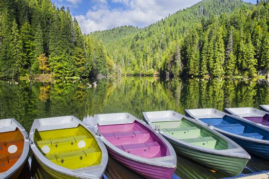 Colorful boats docked on a mountain lake, green forest mirroring in lake. Natural dam lake in forest, Red Lake in Romania