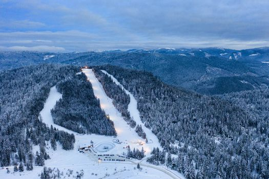 Ski slope and frozen forest in Borsec sports resort, aerial view in the evening.