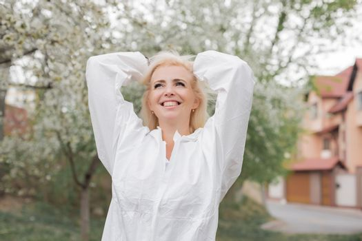 Happy woman in white protective suit among spring garden