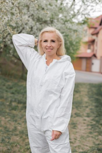 Happy woman in white protective suit among garden