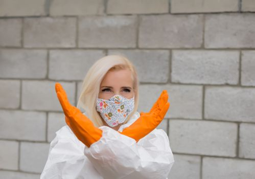 Woman in black mask, white protective suit and gloves