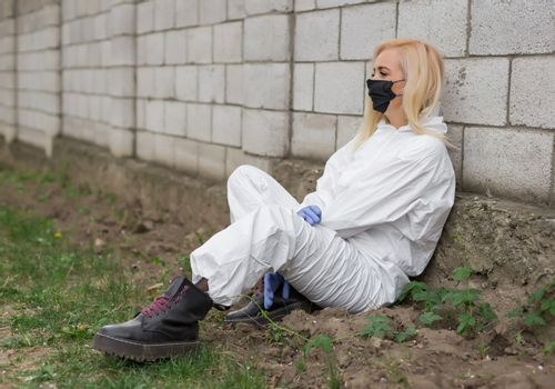 Woman in black mask, white protective suit sitting