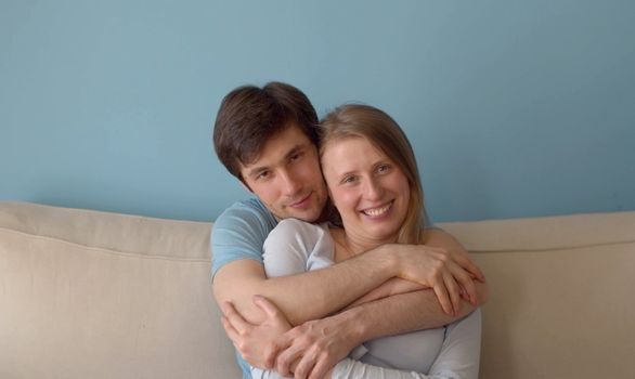 Nice happy family in love hugging in bright room. Young caucasian couple sitting on the sofa and enjoying togetherness