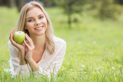 Woman with apple laying on green grass, background with copy space