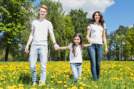 Family of three walking on spring meadow of blooming yellow dandelion flowers being happy
