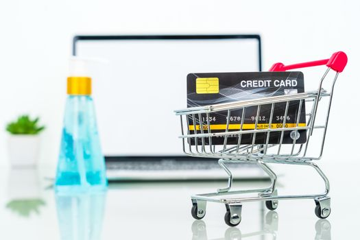 Credit card front of laptop screen with hand sanitizer and surgical mask online shopping, Quarantine work from home concept against covid-19 epidemic