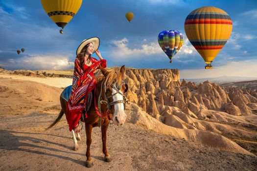 Tourists enjoy ride horses and looking to balloons in Cappadocia, Turkey