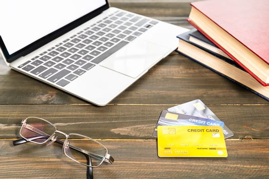 Credit card and notebook keyboard and eyeglasses on wood table