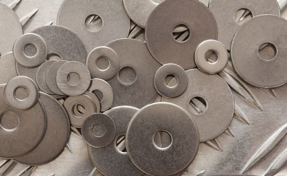 Scattered metal washers on a not slip steel grid