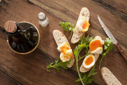 Snack of hard boiled eggs and herbs on baguette