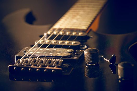 Closeup pickup of the guitar makes the sound amplified louder when connected to speaker. Black vintage electric guitar in dark. Concept of good memory About retro musical instruments and rock music.