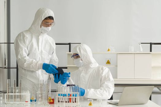 Epidemiological researchers in virus protective clothing use tablet computers to research chemical compounds on the internet. Working atmosphere in chemical laboratory.