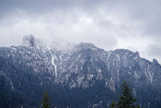 New snow cover on mountain summit, white rocky mountain in Romanian Carpathians.