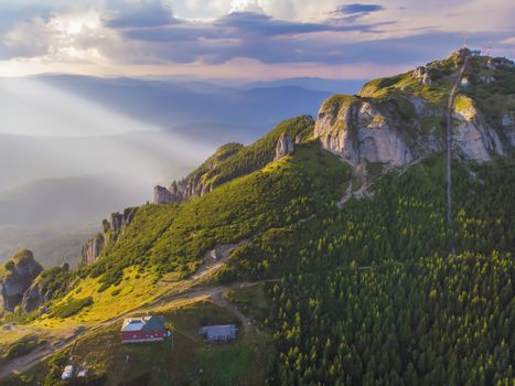 Aerial view of mountain chalet and peak stairs at sunset in Romanian Carpathians.