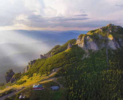 Sunset landscape from above, mountain chalet and rocky peak in Romanian Carpathians.