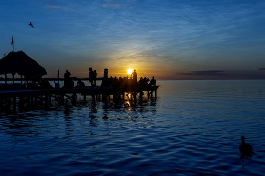 people on a jetty at sunset