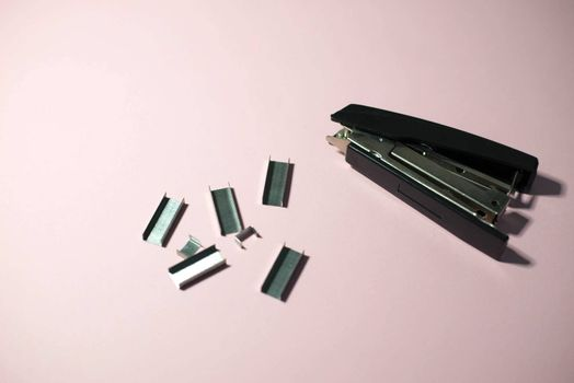 Black stapler on a pink background